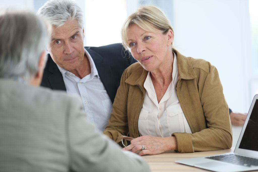 An elderly couple talks to a mortgage lender.